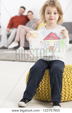 Happy boy sitting on yellow pouffe holding picture, in the background man and woman sitting on sofa