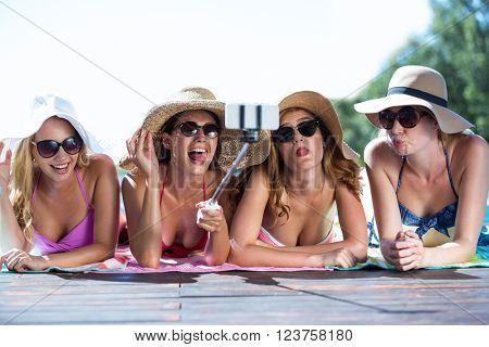 Group of friends taking selfie with selfie stick near pool