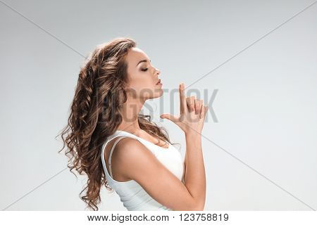 The portrait of violent and militant woman on gray. girl's hands folded gun
