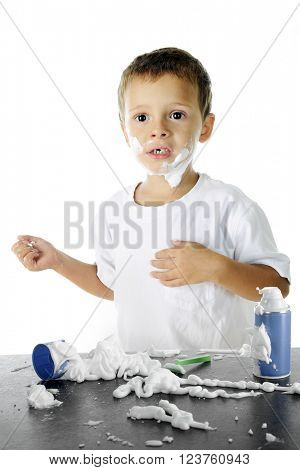An adorable preschooler looking worried in the midst of the shaving cream mess he's made as he attempts to shave like his dad.  On a white background.
