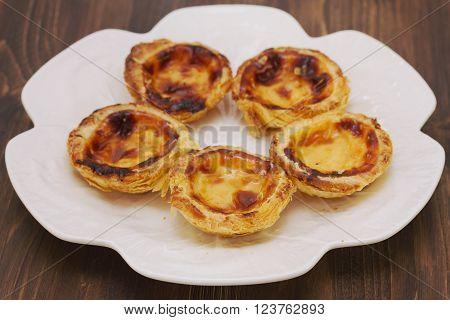 portuguese dessert pasteis de nata on white dish on brown wooden background