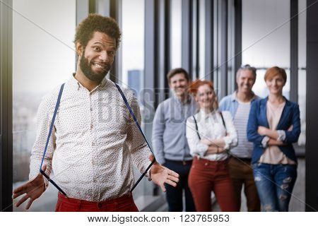 Corporate portrait of young black hipster businessman stretching braces, with his colleagues in background. Post processed with vintage film and sun filter.