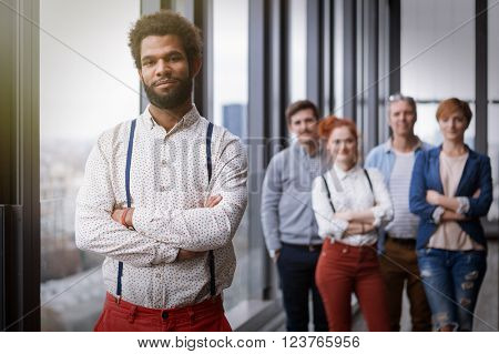 Corporate portrait of young black hipster businessman with his colleagues in background. Post processed with vintage film and sun filter.