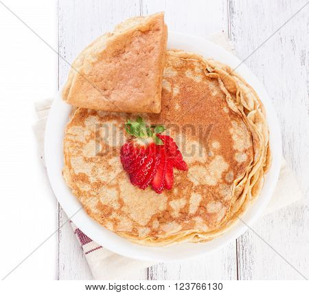 Staple of wheat golden yeast pancakes or crepes traditional for Russian pancake week with fresh strawberry on a wooden table on a white background with place for text or copy space top view