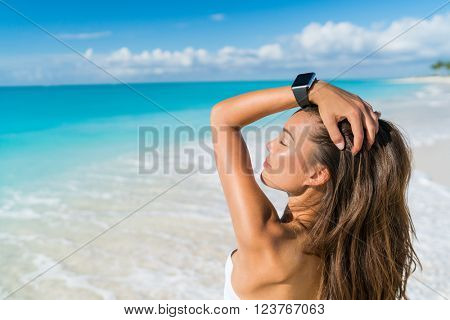 Smartwatch woman relaxing on beach wearing smart wrist watch for activity tracker for an active lifestyle on tropical Caribbean travel destination during summer vacation. Sexy Asian model sun tanning.