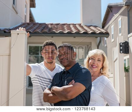 Closer view of multiracial family posing in yard featuring dad with arms crossed.