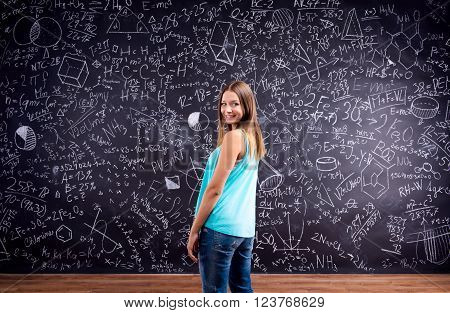 Student girl  in blue singlet against big blackboard with mathematical symbols and formulas, back view, rear view