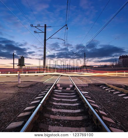 Rail Crossing With Blurred Car Lights At Beautiful Sunset. Railway