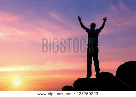 Silhouette Of A Man With Raised-up Arms At The Sunset