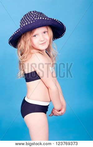 Cute kid girl 4-5 year old wearing hat and swim suit over blue. Looking at camera. Summer time.