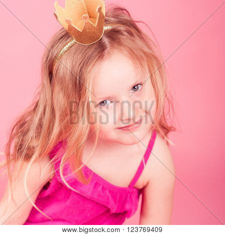 Smiling baby 5-6 year old wearing golden crown over pink background. Looking at camera. Birthday party. Childhood.
