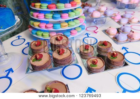 Candy bar on gender reveal party delicious cakes. Dessert table on wedding or party. Closeup assortment of lots of multicolored tasty sweets dessert.
