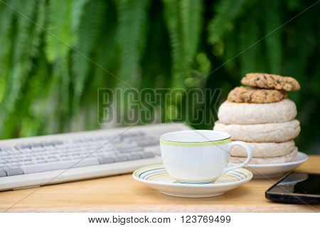 cup of coffee with brad cookie on wood table green fern background