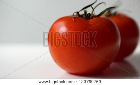 Two fresh red tomatos isolated on white background
