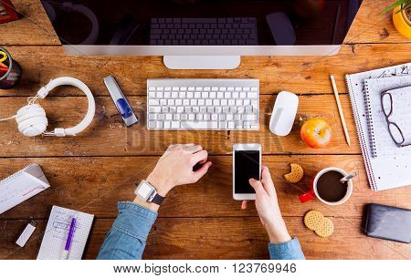 Business person working at office desk. Smart watch on hand, holding a smart phone. Coffee cup, notepad and eyeglasses and various office supplies around the workplace. Flat lay.