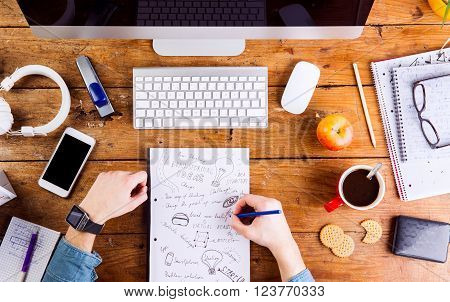 Business person at office desk writing and working. Smart watch on hand and smart phone on the table. Coffee cup, notepad and eyeglasses and various office supplies around the workplace. Flat lay.