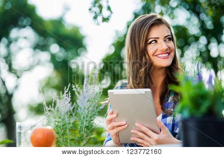 Beautiful gardener with tablet, managing supplies, outside in garden, green sunny nature