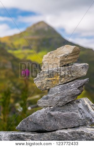 Small cairn with green mountain at background
