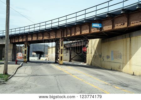JOLIET, ILLINOIS / UNITED STATES - APRIL 12, 2015: Motorists and pedestrians may pass under a railroad bridge in downtown Joliet.
