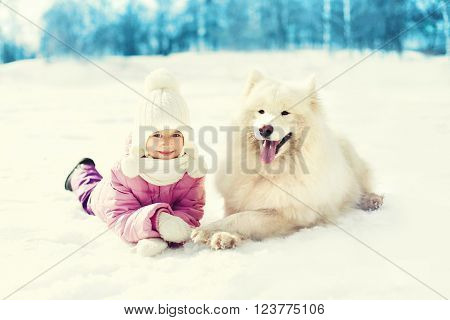 Happy Child With White Samoyed Dog Lying On Snow In Winter Day