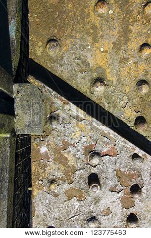 an industrial grunge metal background with flaking yellow paint and rivets