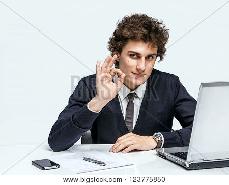 Cheerful young businessman showing Its Okay. Businessman at the workplace working with computer on gray background.