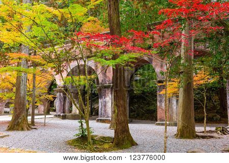 Kyoto, Japan at the Nanzenji Temple aqueduct behind autumn foliage.
