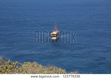 White ship with two masts in bright blue sea near bank of Bali.