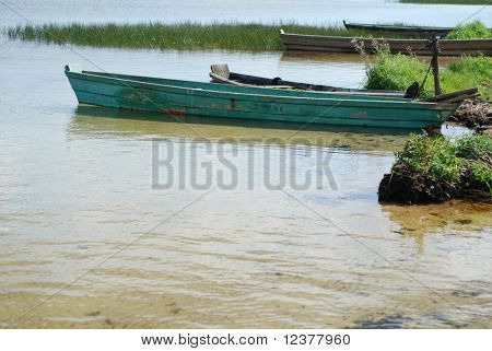 old wooden fishing boat on coast of river in countryside