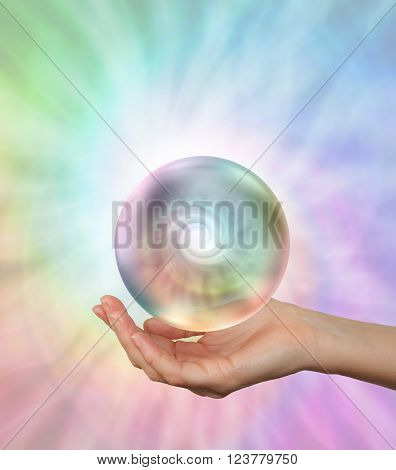 Magical Floating Orb with rainbow spiral energy - female hand outstretched with a hypnotic orb hovering above containing an energy spiral formation on a light rainbow vortex  background