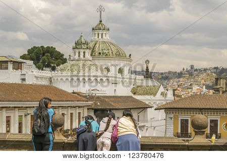 QUITO ECUADOR OCTOBER - 2015 - Group of teens watching from San Francisco church the cityscape view and metropolitan cathedral of the historic center of Quito in Ecuador.