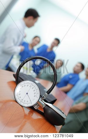 Concept the hospital routine work. Sphygmomanometer on background of briefings doctors