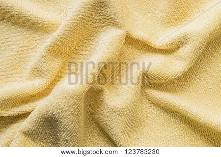 Closeup surface wrinkled yellow napkin fabric background