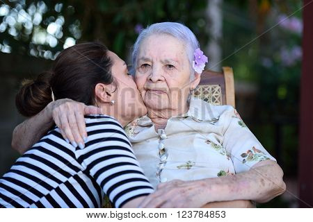 Grandaughter happy kissing her grandma in cheek