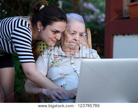 girl and grandma look into modern laptop