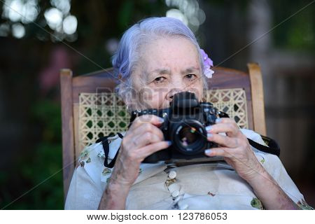 grandma play with DSLR camera sit in park