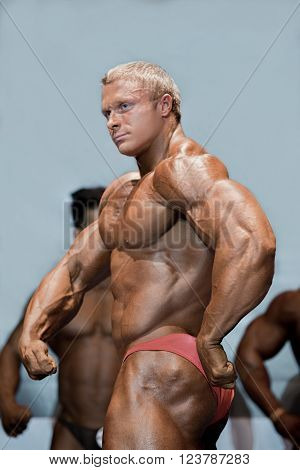 Young bodybuilder in side pose. Male athlete posing on stage. Key moment of performance. Strength and composure.