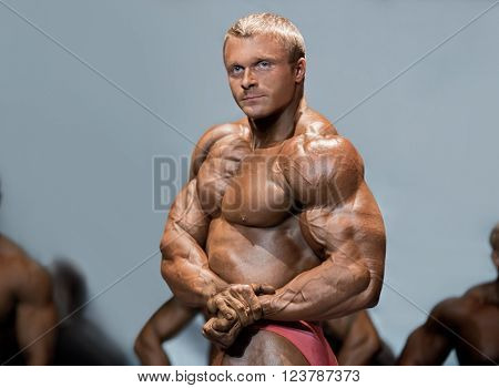 Man flexes chest and arms. Bodybuilder in front of competitors. Great muscle definition. High level bodybuilding competition.