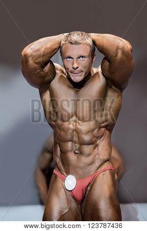 Muscular male flexing abs. Bodybuilder with abs posing. Aesthetic proportions of young athlete. Man dedicated to sport.