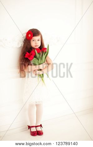 Beautiful baby girl 4-5 year old standing in room holding red tulips. Looking at camera. Mothers day. Childhood.