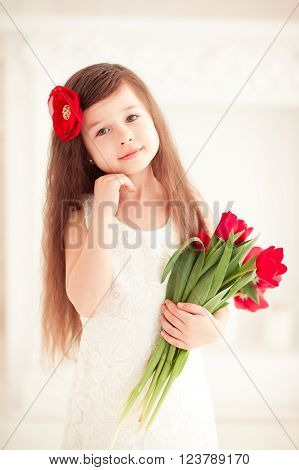 Smiling baby girl 4-5 year old holding flowers in room over white. Cute kid with red tulips. Looking at camera. Wearing white dress, Spring season. 8 of March.