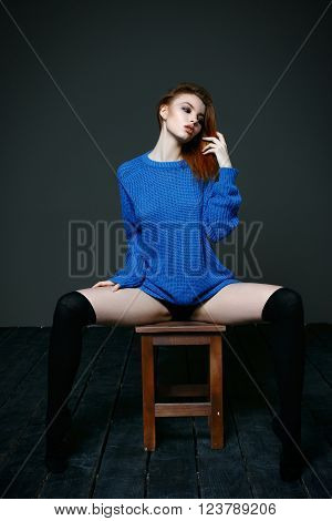 Young beautiful woman posing in blue knitted sweater sitting on chair