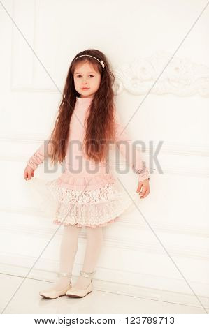 Cute baby girl 4-5 year old wearing pink stylish dress over white looking at camera. Little princess. Childhood.