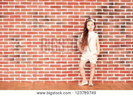 Stylish kid girl 4-5 year old posing over red brick wall looking at camera. Childhood.