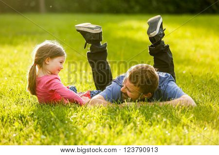 Devoted father and daughter enjoying eachothers company bonding talking having fun in nature on a bright sunny day. Parenthood lifestyle parenting childhood and family life concept.