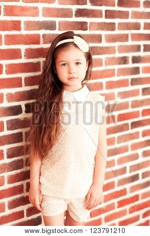 Beautiful baby girl 5-6 year old wearing stylish clothes in room over brick wall looking at camera. Childhood. ** Note: Soft Focus at 100%, best at smaller sizes