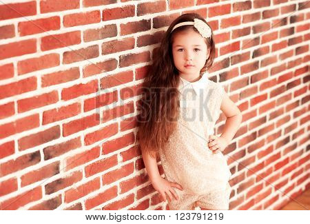 Beautiful baby girl 4-5 year old posing in room leaning on brick wall looking at camera. Childhood.