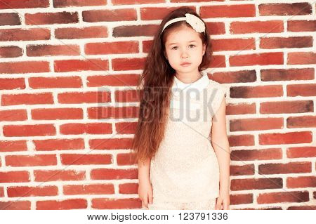 Cute kid girl 5-6 year old wearing style clothes over brick wall looking at camera. Childhood.