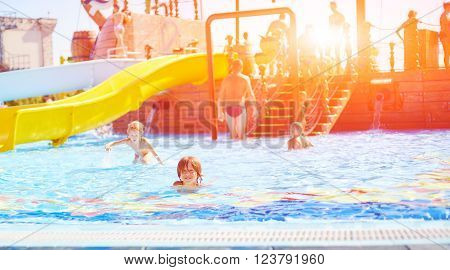 children in pool at sunny summer day. children playing in water. Vacation and traveling with kids. Children play outdoors in summer.