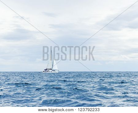 Sailing yacht floating in sea along skyline